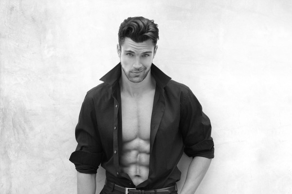 Very sexy male model with open shirt revealing muscular body and