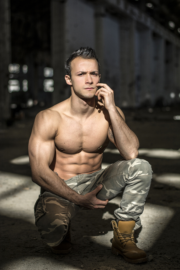 Muscular shirtless young man in abandoned warehouse sitting looking at camera