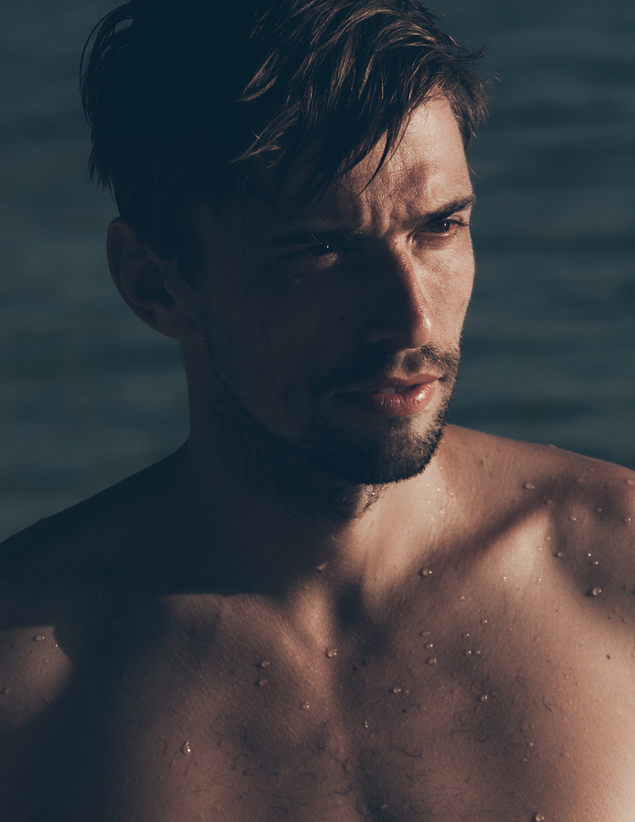 Close-up portrait of a sexy handsome Caucasian young man, bearded and tanned, posing shirtless while looking aside, in a hot sunny day at the seaside