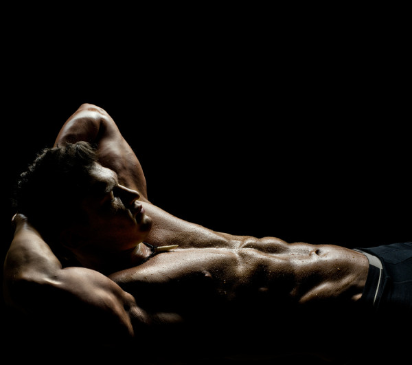 the very muscular sleeping sexy guy lying on black background naked torso