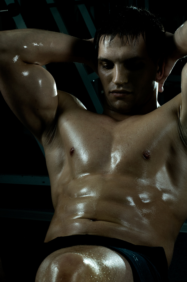 very power athletic guy ,  execute exercise on muscles belly, in  sport-hall, beauty glamour light