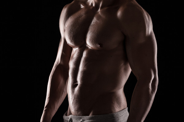 Strong Athletic Man Fitness Model Torso showing six pack abs. isolated on black background