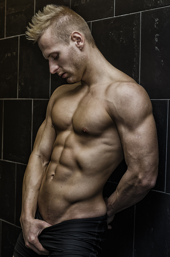 Handsome, muscular young man shirtless leaning against tiled wall, looking at camera