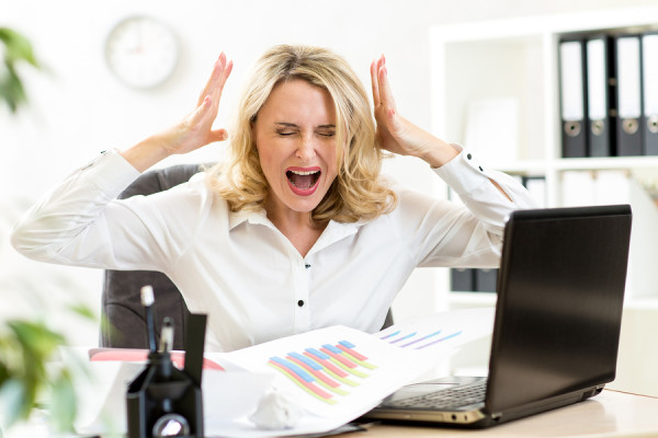Stressed business woman screaming loudly at laptop in office
