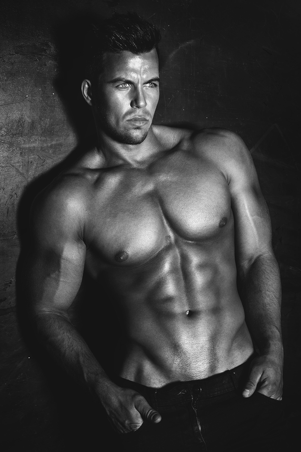 Sexy fashion portrait of a hot male model with muscular body posing in studio looking at camera.