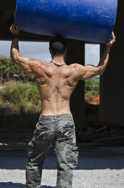 Muscular construction worker shirtless in building site holding big blue barrel over his head shot from the back ** Note: Soft Focus at 100%, best at smaller sizes