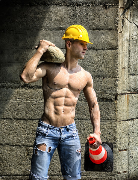 Handsome muscular young construction worker shirtless outdoor holding stone and traffic cone ** Note: Soft Focus at 100%, best at smaller sizes
