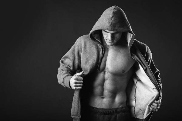 Young muscular man with open jacket revealing muscular chest and abs.Portrait of a muscular young man in hood jacket posing on black background.Young man with athletic body posing on black background