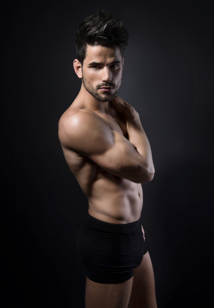 handsome young muscular man posing shirtless while showing of his muscles