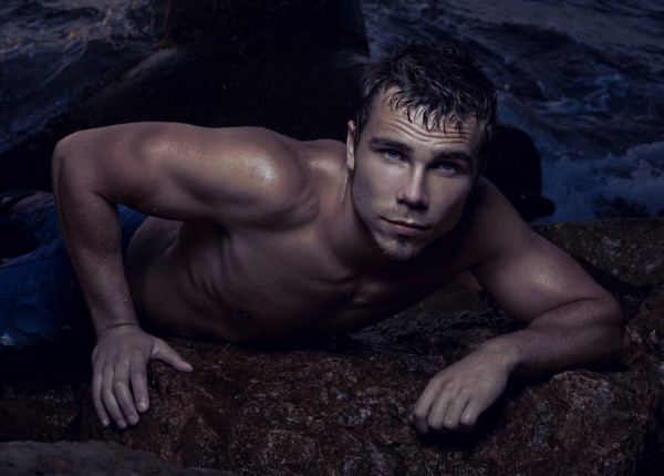 Sexy boy sits on a rock in the sea.