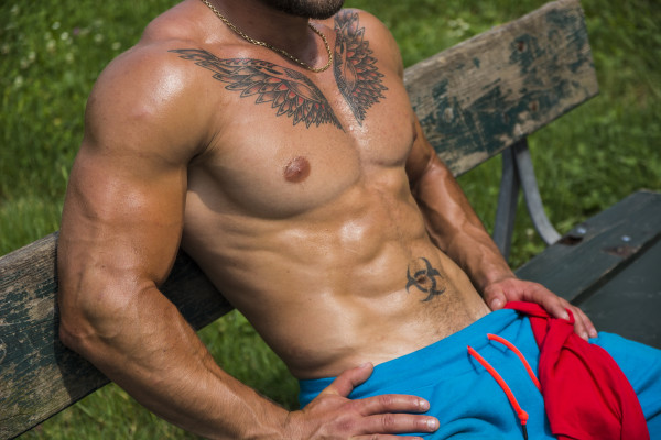 Muscular Shirtless Hunk Man Outdoor in City Park. Showing Healthy Muscle Body