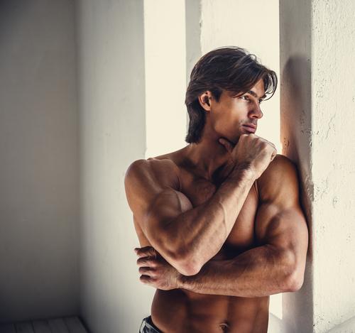Portrait of thoughtful muscular male near window in daylight.