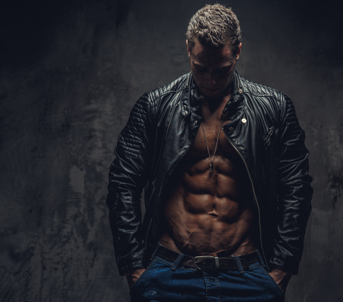 Muscular male in blue jeans and black jacket wearing on shirtless body. Isolated on grey background.