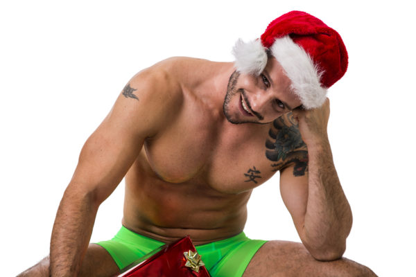 Muscular shirtless young man in Santa Claus hat standing holding two colorful festive Christmas gifts to celebrate the season, isolated on white