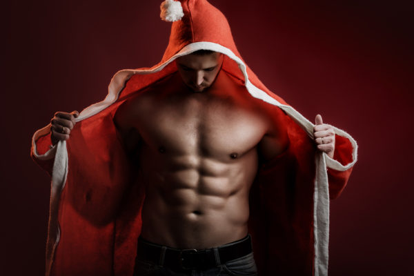 One sexual strong young new year man with muscular body in red and white christmas santa coat standing posing on studio background horizontal picture