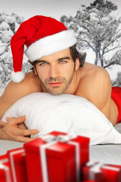 Sexy man in santa cap relaxing in bed with fantastical winter background and red wrapped gifts in foreground
